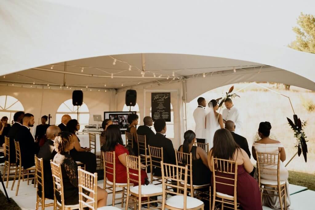 Tent wedding ceremony Omaha, Nebraska.  Outdoor ceremony.  Wedding invitations by Dana Osborne Design.