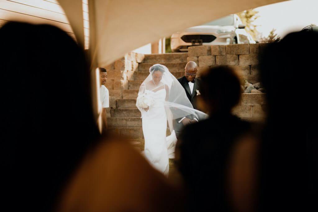 Bride with father walking down the aisle, outdoor backyard wedding.  Omaha, Nebraska.  Invitations by Dana Osborne Design.