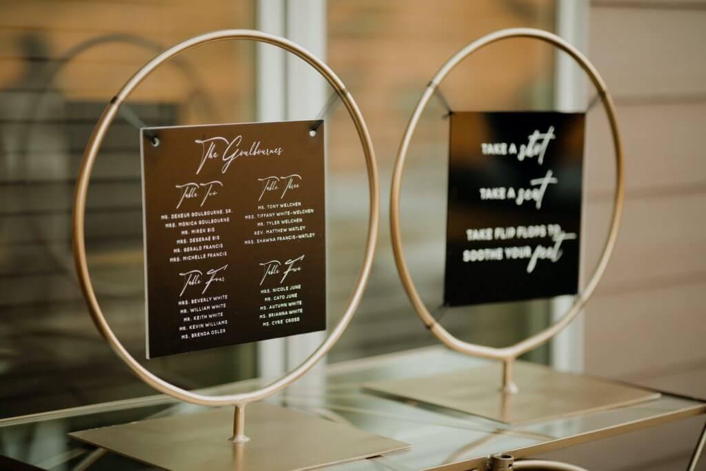 Black acrylic seating chart and flip flop sign. Omaha backyard wedding.   www.danaosbornedesign.com